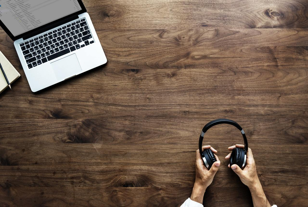 Bluetooth Kopfhörer mit MacBook auf einem Schreibtisch