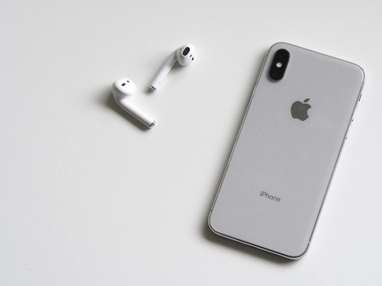 Es liegen ein paar Apple AirPods neben einem iPhone